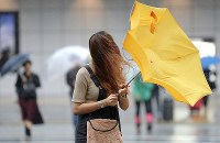 A woman's umbrella is blown inside out as a result of strong winds brought by Typhoon Hagibis, in Tokyo's Shinjuku Ward on the morning of Oct. 12, 2019. (Mainichi/Yuki Miyatake)