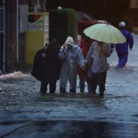 冠水した道路から避難する人たち=川崎市高津区で2019年10月12日午後5時3分、小川昌宏撮影