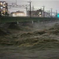 台風19号の接近で増水した多摩川。奥は運行を停止しているJR中央線の鉄橋=東京都日野市で2019年10月12日午後5時半、内林克行撮影