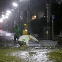 台風19号による大雨で、冠水した住宅地を手をつきながら歩く男性=東京都世田谷区で2019年10月12日午後9時34分、共同