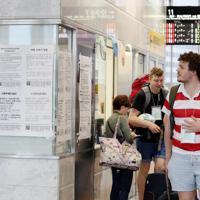 台風19号の接近で鉄道の運転が一部見合わせになったことを知らせる掲示に見入る外国人観光客=大阪市北区のJR大阪駅で2019年10月12日午前8時49分、幾島健太郎撮影