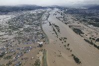 Houses are seen submerged in the Hoyasu district of Nagano, Nagano Prefecture, in central Japan, after the Chikuma River overflowed due to Typhoon Hagibis, in this photo taken from a Mainichi Shimbun helicopter on the morning of Oct. 13, 2019. A breached embankment is seen at the lower center of the image. (Mainichi)
