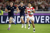 Japan's Kenki Fukuoka, right, scores a try during the Rugby World Cup Pool A game at International Stadium against Scotland in Yokohama, Japan, Sunday, Oct. 13, 2019. (AP Photo/Jae Hong)