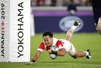 Japan's Kenki Fukuoka scores a try during the Rugby World Cup Pool A game at International Stadium against Scotland in Yokohama, Japan, Sunday, Oct. 13, 2019. (AP Photo/Jae Hong)