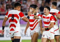 Japan's Kenki Fukuoka is congratulated by teammate Kazuki Himeno, left, after scoring his second try during the Rugby World Cup Pool A game at International Stadium between Japan and Scotland in Yokohama, Japan, Sunday, Oct. 13, 2019. (AP Photo/Christophe Ena)