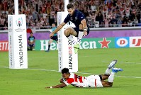 Scotland's Tommy Seymour leaps over Japan's Kotaro Matsushima as he scores a try during the Rugby World Cup Pool A game at International Stadium between Japan and Scotland in Yokohama, Japan, Sunday, Oct. 13, 2019. (AP Photo/Christophe Ena)