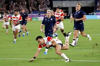 Japan's Kenki Fukuoka crosses for his team's third try during the Rugby World Cup Pool A game at International Stadium between Japan and Scotland in Yokohama, Japan, Sunday, Oct. 13, 2019. (AP Photo/Christophe Ena)