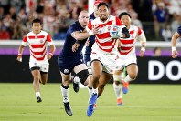 Japan's Timothy Lafaele, center, runs with a ball during the Rugby World Cup Pool A game at International Stadium between Japan and Scotland in Yokohama, Japan, Sunday, Oct. 13, 2019. (AP Photo/Eugene Hoshiko)
