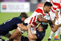 Japan's Timothy Lafaele is tackled by Scotland defenders during the Rugby World Cup Pool A game at International Stadium between Japan and Scotland in Yokohama, Japan, Sunday, Oct. 13, 2019. (AP Photo/Christophe Ena)