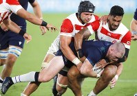 Scotland's Stuart Hogg is tackled by Japanese defenders during the Rugby World Cup Pool A game at International Stadium between Japan and Scotland in Yokohama, Japan, Sunday, Oct. 13, 2019. (AP Photo/Christophe Ena)