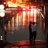 台風19号の影響で冠水した住宅街の道路。奥には緊急車両が並んでいた=東京都世田谷区で2019年10月13日午前0時20分、小川昌宏撮影