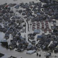 千曲川の堤防が決壊し、浸水する長野市豊野町豊野の住宅街=2019年10月13日午前8時9分、本社ヘリから