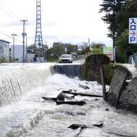 郡山市の住宅地では道路の一部が陥没し、水が滝のように流れ落ちていた=郡山市富久山町久保田で2019年10月13日午前8時18分、渡部直樹撮影