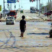 秋山川が決壊し、激しく水が流れる路上に立つ男性=栃木県佐野市で2019年10月13日午前10時19分、小川昌宏撮影