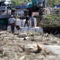 台風19号の影響で、秋山川の決壊した場所を埋めるための土のうを積む作業が行われた=栃木県佐野市で2019年10月13日午前11時37分、小川昌宏撮影