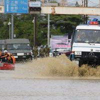 千曲川の堤防が決壊して浸水した住宅街から住民たちを救助する警察車両(右)=長野市大町付近で2019年10月13日午後1時54分、丸山博撮影