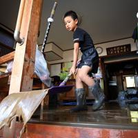 台風19号の影響で床上浸水した祖父宅で、泥水で汚れた敷物を片付ける小谷駿さん(9)。祖父の市川恵一さん(72)は「(片付けを)いくらやっても下から泥水が出てくる」と話した=栃木県佐野市で2019年10月13日午後2時20分、小川昌宏撮影