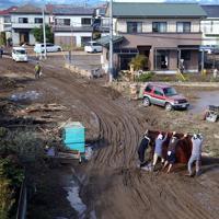 台風19号の影響で秋山川が氾濫し、道路や住宅地に残った土砂などを撤去する人たち=栃木県佐野市で2019年10月13日午後2時5分、小川昌宏撮影