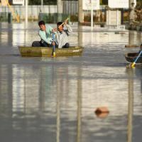 千曲川の堤防が決壊して浸水した住宅街をボートで移動する住民=長野市下駒沢付近で2019年10月13日午後3時27分、丸山博撮影