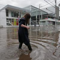 ラグビー・ワールドカップのファンゾーンとなっている釜石市民ホール(奧)前の冠水した道路を歩く女性=岩手県釜石市で2019年10月13日午前8時26分、和田大典撮影
