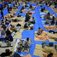 千曲川の堤防決壊で家が浸水した大勢の人が避難している体育館=長野市豊野町の豊野西小学校で2019年10月13日午後6時31分、丸山博撮影