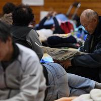 避難所で新聞に見入る男性=長野市豊野町の豊野西小学校で2019年10月13日午後6時13分、丸山博撮影