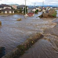 堤防が決壊し、秋山川(右)の水が住宅街に流れ込んでいる=栃木県佐野市で2019年10月13日午前7時50分ごろ、玉井滉大撮影