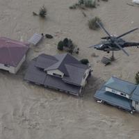 浸水した市街地を警戒する自衛隊のヘリ=長野市穂保地区で2019年10月13日午前8時16分、本社ヘリから