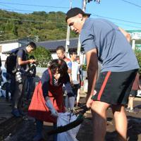 冠水した道路から泥をかき出すカナダ代表のジョシュ・ラーセン(右)=岩手県釜石市千鳥町1で2019年10月13日、中尾卓英撮影