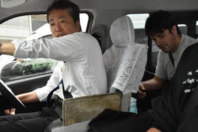 AI配車のタクシーに乗り込むイタリア人観光客(右奥)=金沢市で、日向梓撮影