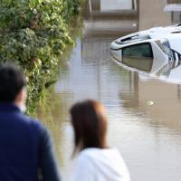 横転し、水につかった車を見つめる人たち=長野市で2019年10月14日午前7時33分、佐々木順一撮影