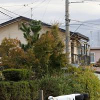 浸水地域で横転した車。奥ではヘリによる救助活動が行われている=長野市で2019年10月14日午前7時31分、佐々木順一撮影