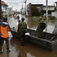 浸水が続く町中心部にある介護老人保健施設へ自衛隊のボートで向かう職員ら。職員によると、施設では1階の浸水が続く中、入所者と職員が2階以上で生活を続けているという。=宮城県丸森町で2019年10月14日午前10時2分、平川義之撮影