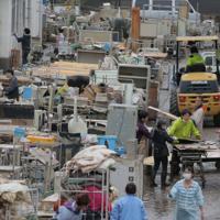 台風19号の影響で川が氾濫し浸水した病院で、机や椅子、ベッドなどを外に運び出す作業をする人たち=福島県本宮市で2019年10月14日午後2時32分、和田大典撮影