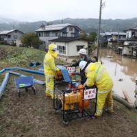 浸水した住宅街から水をくみ上げて川に流す消防団員ら=長野市で2019年10月14日午後3時51分、佐々木順一撮影
