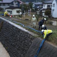 浸水した住宅街から水をくみ上げて川に流す消防団員ら=長野市で2019年10月14日午後3時59分、佐々木順一撮影