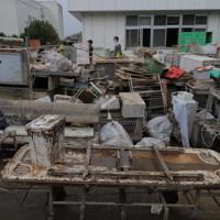 台風19号の影響で川が氾濫し浸水した病院で、机や椅子、ベッドなどを外に運び出す作業をする人たち=福島県本宮市で2019年10月14日午後2時4分、和田大典撮影