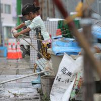 台風19号の影響で阿武隈川が氾濫して浸水した地域で、ぞうきんを絞る子ども。泥水につかった母親の実家の掃除を手伝うため隣町から駆けつけた=福島県本宮市で2019年10月14日午後3時7分、和田大典撮影