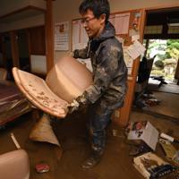 千曲川の堤防が決壊して濁流が流れ込んだ住宅の片付けをする男性=長野市穂保で2019年10月14日午後3時56分、丸山博撮影