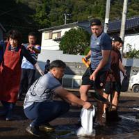 冠水した道路から、スコップを持って泥をかき出すカナダ代表のジョシュ・ラーセン選手(中央)ら=釜石市千鳥町で