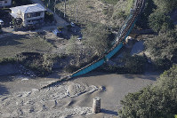 An iron bridge serving the JR Suigun Line between Fukuroda and Hitachi-Daigo stations, a mountainous area of Ibaraki Prefecture, is seen collapsed into the Kuji River due to Typhoon Hagibis, in this photo taken from a Mainichi Shimbun helicopter on Oct. 13, 2019. (Mainichi)