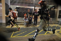 Police chase a protester in Hong Kong, on Oct.13, 2019. Protesters changed tactics and popped up in small groups in multiple locations across the city Sunday rather than gather in one large demonstration. (AP Photo/Kin Cheung)