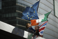 Two anti-Brexit people hold EU, Ireland and Union Flags stand outside the European Commission in Brussels, on Oct. 11, 2019. (AP Photo/Francisco Seco)