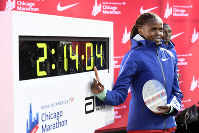 Brigid Kosgei of Kenya, poses with her time after winning the Women's Bank of America Chicago Marathon while setting a world record of 2:14:04, on Oct. 13, 2019, in Chicago. (AP Photo/Paul Beaty)
