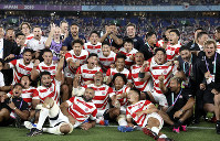 Japan players and management celebrate after defeating Scotland 28-21 in their Rugby World Cup Pool A game at International Stadium in Yokohama, Japan, Oct. 13, 2019. (AP Photo/Christophe Ena)