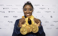 Simone Biles of the United States shows her five gold medals at the Gymnastics World Championships in Stuttgart, Germany, on Oct. 13, 2019. (Marijan Murat/dpa via AP)