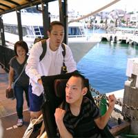 車椅子の権田祐也さんは、兵庫県淡路市から高速船に乗ってやって来た。後ろは介助する李昭世さん=兵庫県明石市で、桜井由紀治撮影
