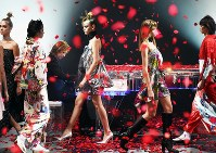 X Japan leader Yoshiki plays a piano while models showcase his kimono fashion brand