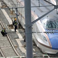 千曲川の堤防が決壊し、浸水した長野新幹線車両センターで車両の状態を確認する作業員=長野市で2019年10月15日午後0時36分、佐々木順一撮影