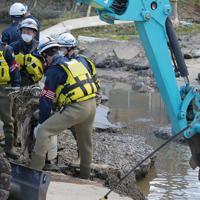 浸水し道路が壊れた現場で安否不明者のものとみられるバイクが見つかり、重機で引き上げた警察官ら。その後付近を捜索した=福島県郡山市で2019年10月15日午後0時34分、和田大典撮影
